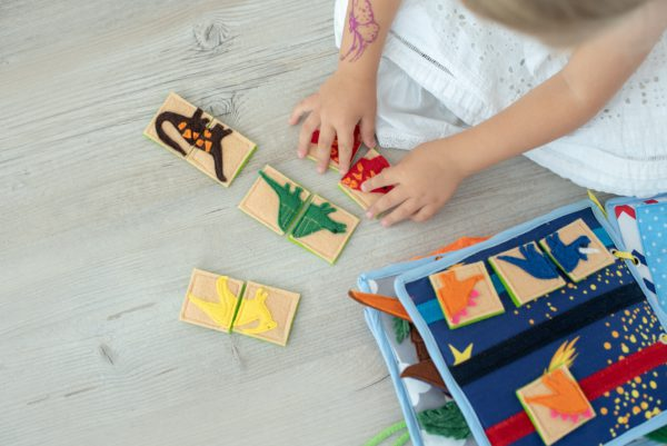 small-girl-playing-puzzle-in-dinosaur-busy-book