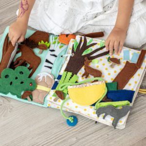 hands-holding-felt-busy-book-with-woodland-animal-toys