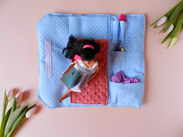 barbie-doll-with-white-dress-sitting-on-pink-blanket-bag-for-doll