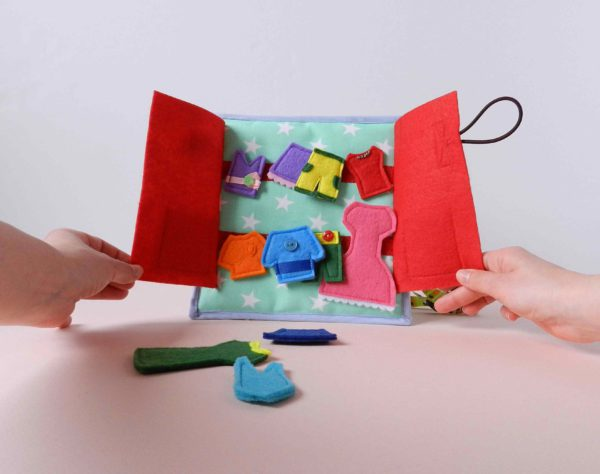 hands-holding-the-quiet-book-page-with-felt-clothes